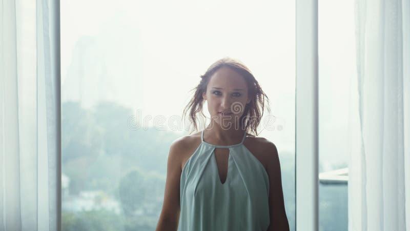 Портрет привлекательного положения коммерсантки перед окнами в улыбках и взглядах офисного здания на камере стоковые изображения rf