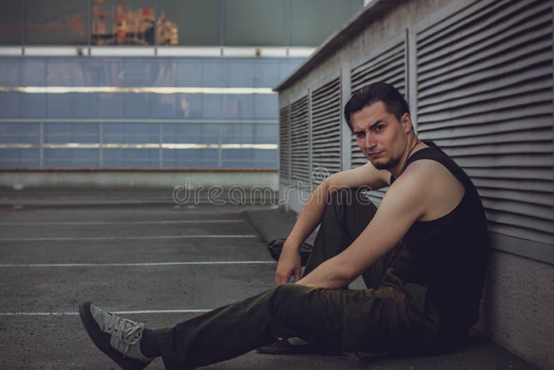 Портрет привлекательного темн-с волосами молодого человека при смешное выражение стороны сидя против городской предпосылки стоковые фотографии rf