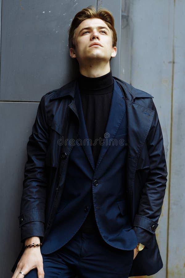 Портрет привлекательного человека, парень, бизнесмен, нося голубой костюм, пальто Руки в карманах, стоимость на улице стоковая фотография