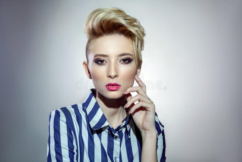 Портрет привлекательной белокурой женщины в striped рубашке представляя на серой предпосылке стоковое фото rf