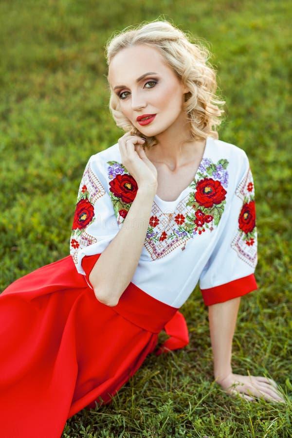 Портрет привлекательной белокурой женщины с макияжем и курчавого стиля причесок в стильном красном белом платье представляя с неж стоковое изображение