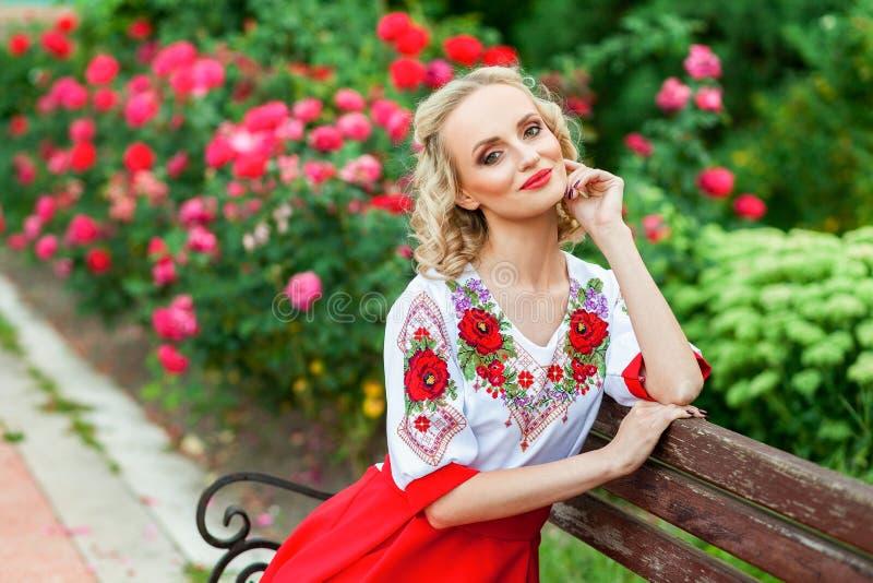 Портрет привлекательной белокурой молодой женщины с макияжем и курчавого стиля причесок в стильном красном белом платье представл стоковая фотография rf
