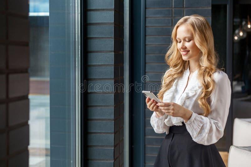 Портрет привлекательной деловой женщины, счастливо улыбающейся при использовании мобильного телефона стоять около окна, в помещен стоковые изображения rf