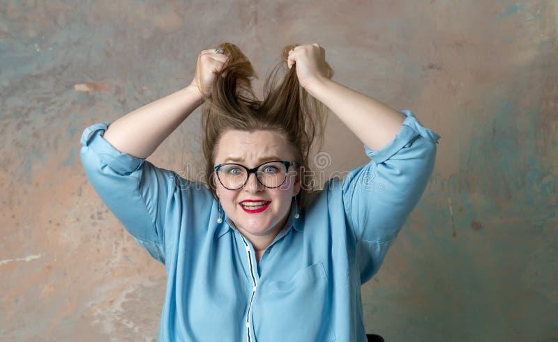 Портрет привлекательной добавочной женщины размера имея эмоции гнева, выражающ безвыходность и раздражение над покрашенный стоковое изображение