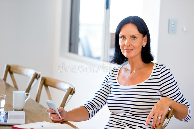 Портрет привлекательной женщины держа телефон стоковое изображение
