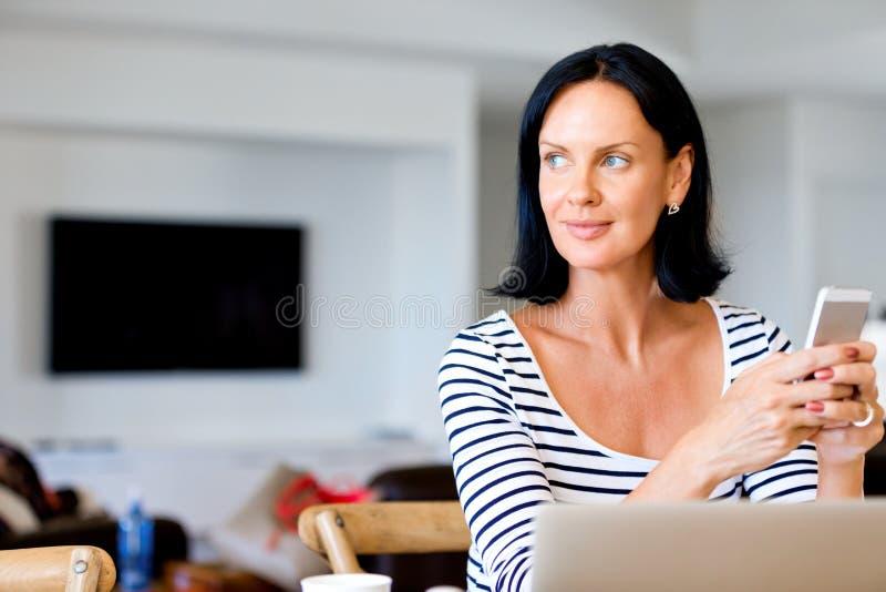 Портрет привлекательной женщины держа телефон стоковые изображения rf