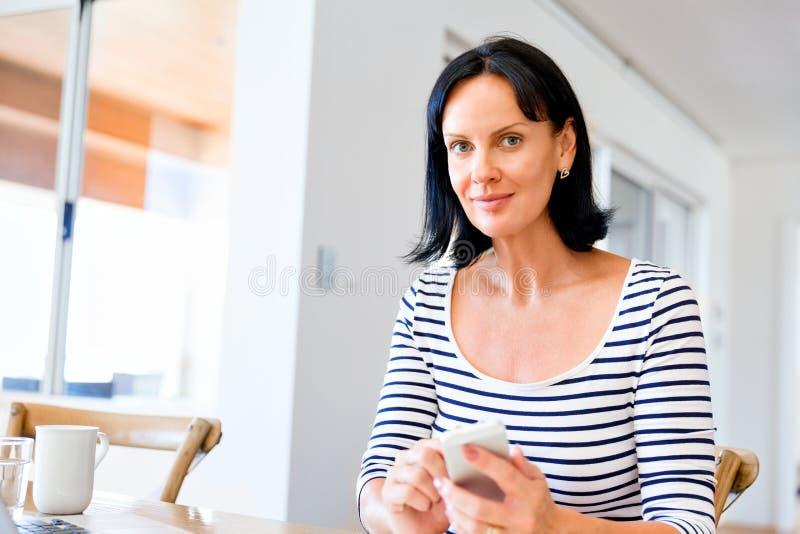 Портрет привлекательной женщины держа телефон стоковые фото
