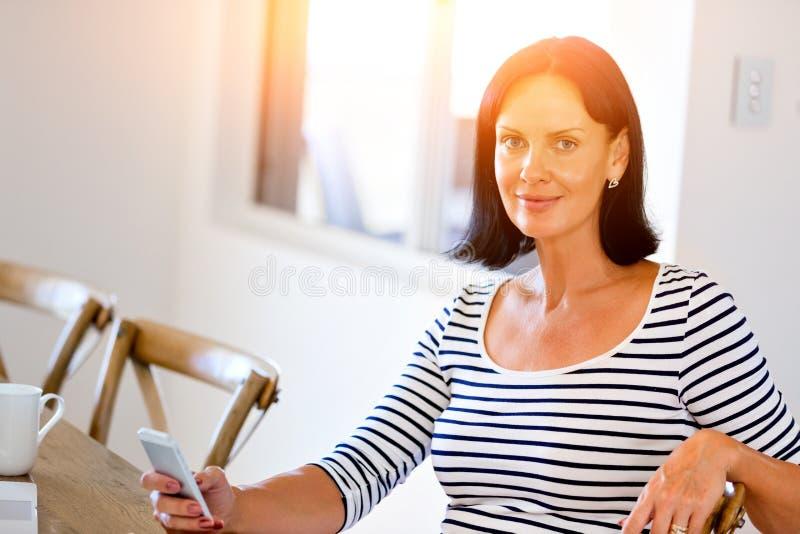 Портрет привлекательной женщины держа телефон стоковое фото