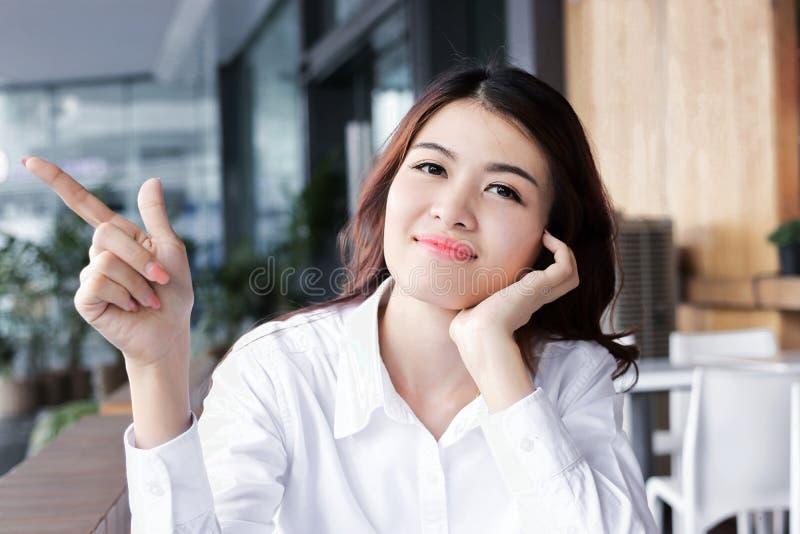 Портрет привлекательной молодой азиатской женщины смотря вперед представляющ и имеет идею в офисе стоковая фотография