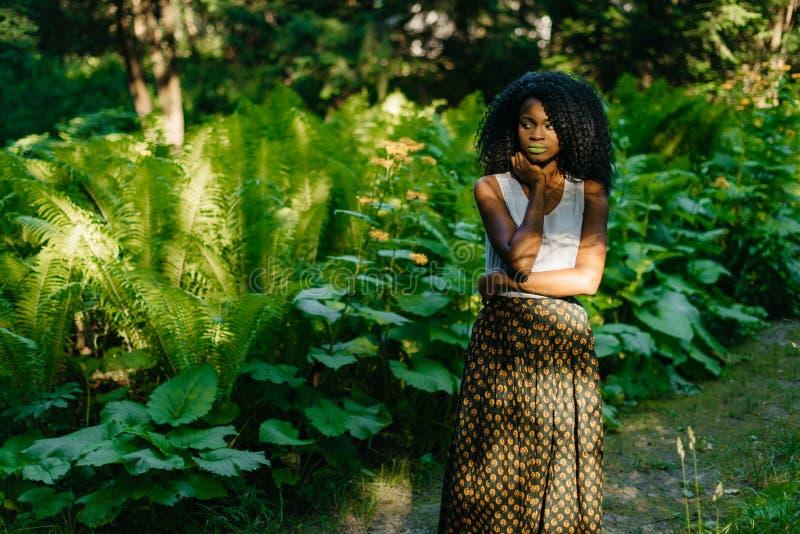 Портрет привлекательной молодой африканской девушки с зеленым составом в стильной одежде заботливо смотря в сторону пока стоковое изображение rf