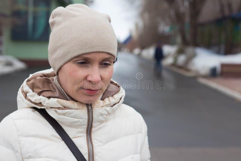 Портрет привлекательной молодой женщины в белых куртке и шляпе, холодном дне стоковые фото