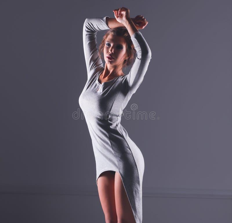 Портрет привлекательной молодой женщины полнометражный изолированный на серой предпосылке стоковая фотография rf