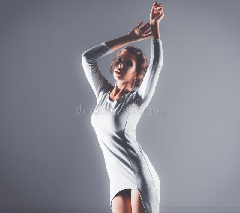 Портрет привлекательной молодой женщины полнометражный изолированный на серой предпосылке стоковое фото rf