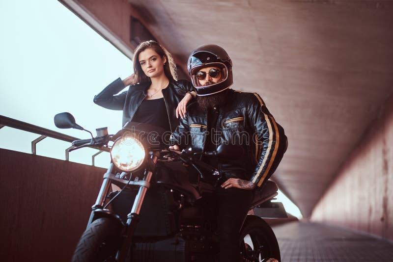 Портрет привлекательной пары - зверский бородатый велосипедист в шлеме и солнечные очки одели в черной кожаной куртке стоковые изображения