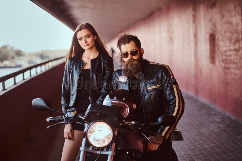 Портрет привлекательной пары - зверский бородатый велосипедист в черной кожаной куртке при солнечные очки сидя на мотоцикле стоковые изображения rf