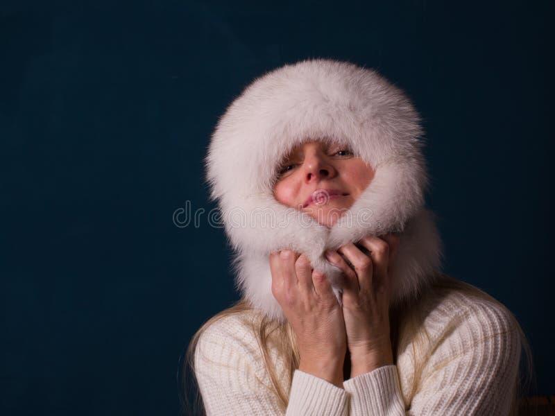 Портрет привлекательной, шаловливой женщины в теплой уборной меховой шапки зимы стоковые изображения rf