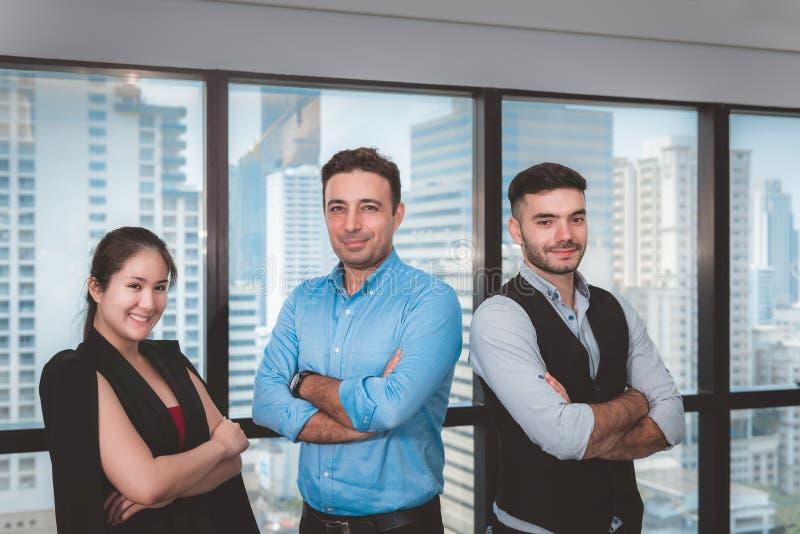 Портрет привлекательных бизнесменов стоит около рамки в современном офисе, уверенной сыгранности Windows дела в оружиях стоковая фотография