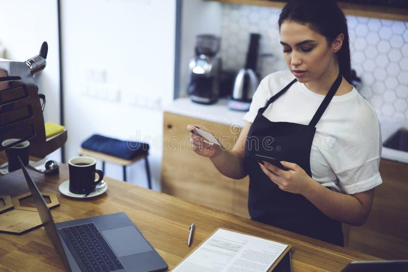 Портрет привлекательного женского barista работая в столовой стоковое изображение