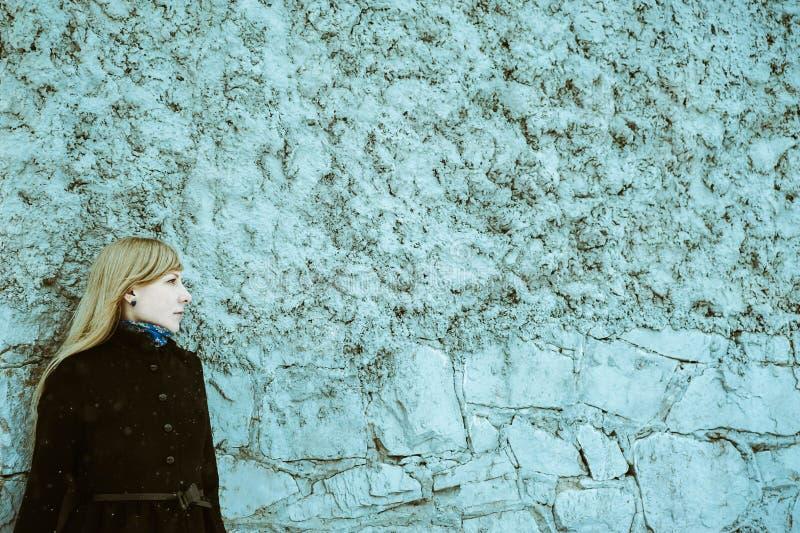 Портрет привлекательной белокурой девушки на предпосылке голубой бетонной стены одел в пальто стоковые изображения rf