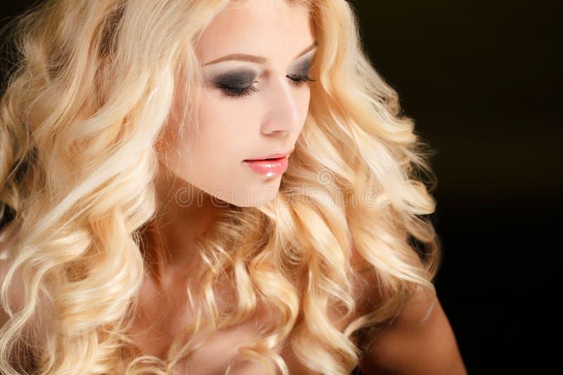 Портрет привлекательной белокурой женщины с длинным вьющиеся волосы, изолированный на черной съемке студии стоковые изображения rf