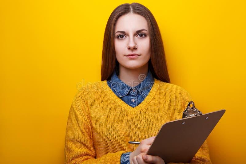 Портрет привлекательной девушки с доской сзажимом для бумаги стоковое изображение rf