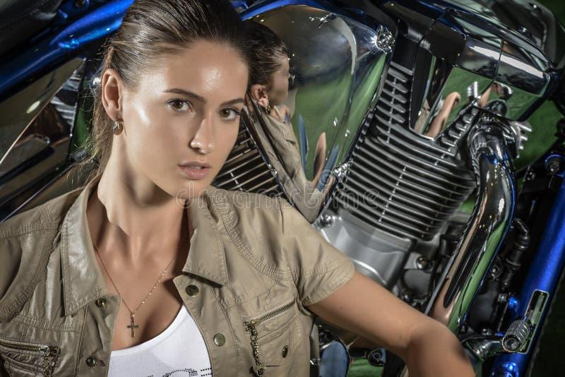 Портрет привлекательной молодой женщины, над предпосылкой мотоцикла стоковое фото rf