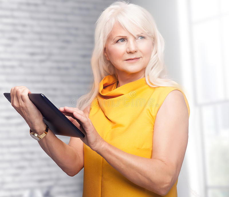 Портрет привлекательной старшей коммерсантки используя таблетку стоковая фотография rf