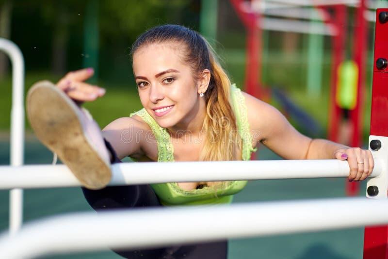 Портрет пригонки и sporty молодой женщины делая протягивать в земле спорт разминки стоковые изображения rf