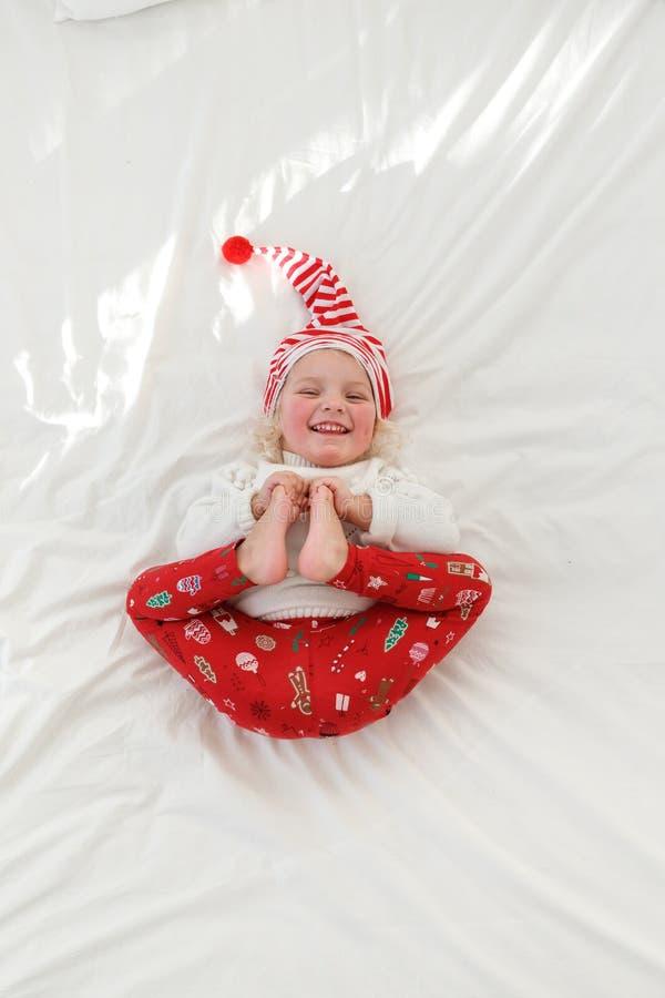 Портрет приятной смотря усмехаясь маленькой девочки носит pyjamas и шляпа эльфа s, держит ноги совместно, лежит на удобной стоковые фотографии rf