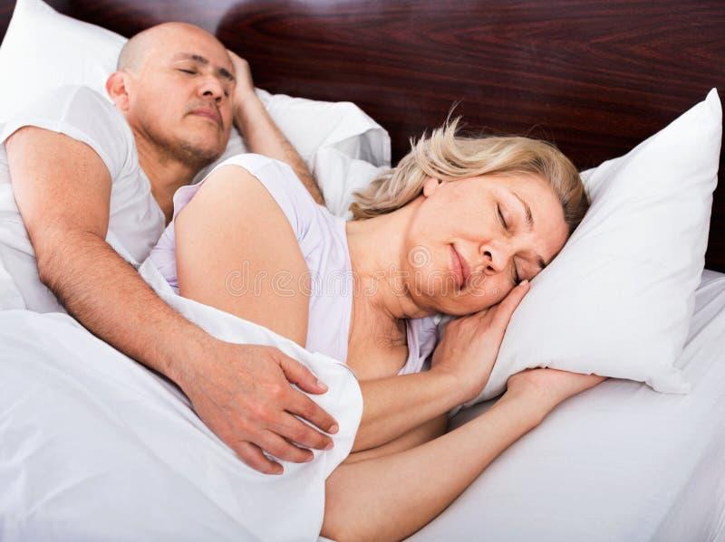 Портрет приятных зрелых пар napping в кровати стоковое фото