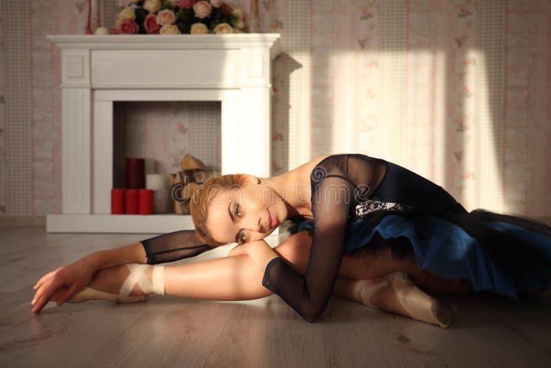 Портрет профессионального артиста балета сидя на деревянном поле в свете солнца Женская балерина имея остатки стоковое фото rf