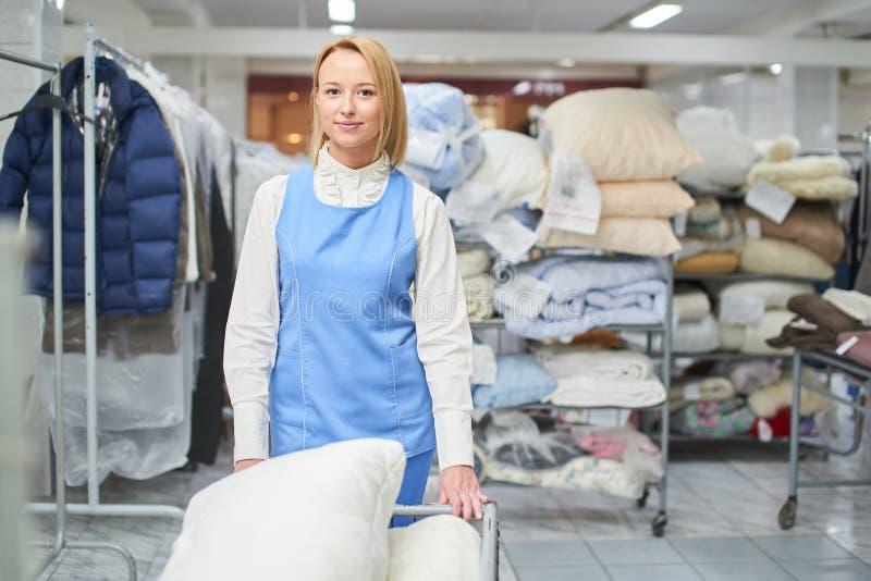 Портрет работника девушки в прачечной склада с чистыми одеждами стоковые изображения