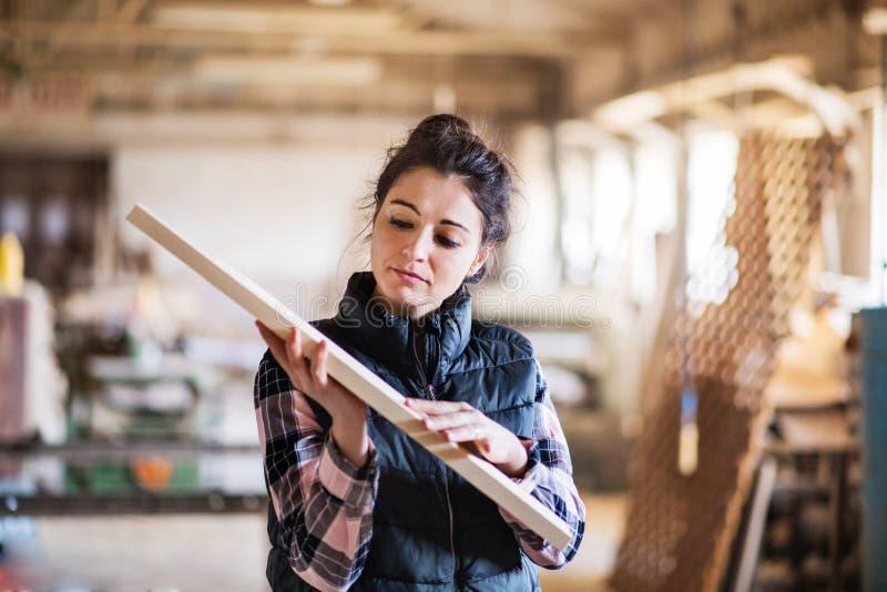 Портрет работника женщины в мастерской плотничества, держа деревянную планку стоковая фотография rf