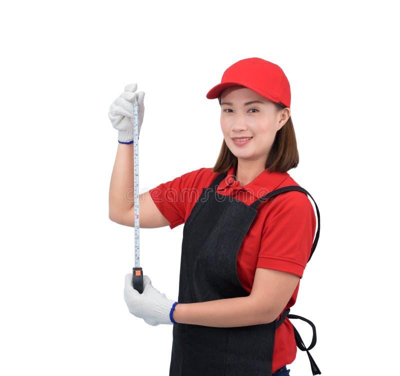 Портрет работника молодой женщины усмехаясь в красной форме с рисбермой, лентой удерживания руки перчатки измеряя изолированной н стоковое изображение