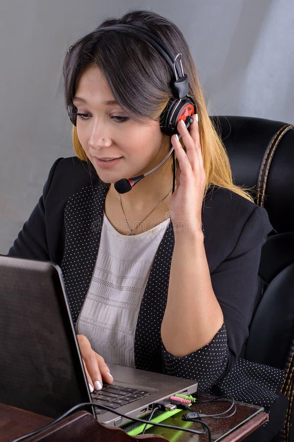 Портрет работника обслуживания клиента женщины, оператора центра телефонного обслуживания усмехаясь с шлемофоном телефона стоковое изображение