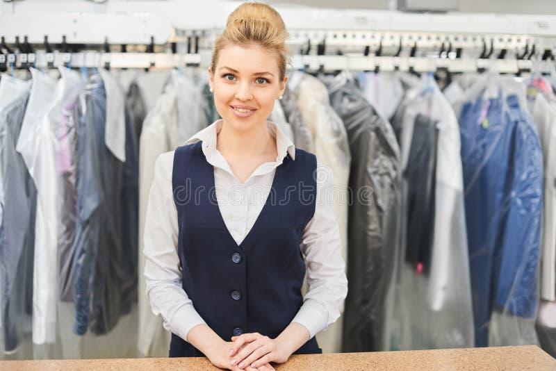 Портрет работника прачечной на предпосылке одежды на вешалках стоковая фотография rf