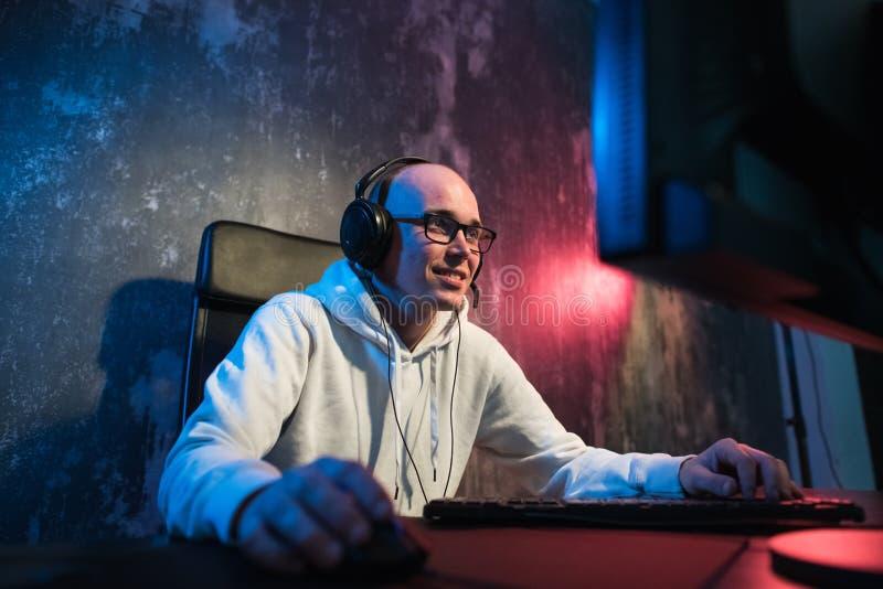 Портрет радостного молодого gamer играя видеоигры дома на компьютере Gamer в наушниках счастлив и показывать стоковое изображение