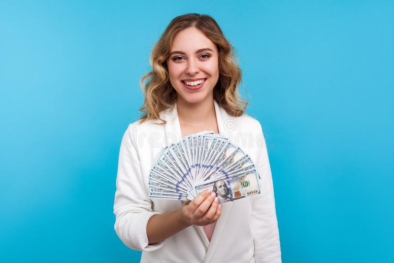 Портрет радостной богатой женщины, держащей доллары и счастливо улыбающейся, получающей доход от инвестиций синий фон стоковые изображения rf