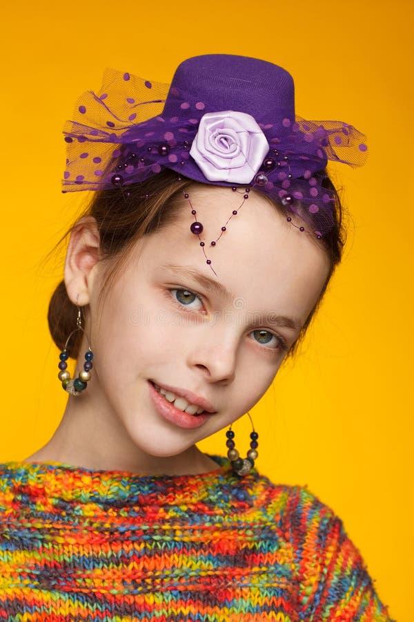 Портрет радостной восьмилетней девочки в миниатюрной шляпе и в свитере с несколькими цветами Желтый фон стоковое изображение