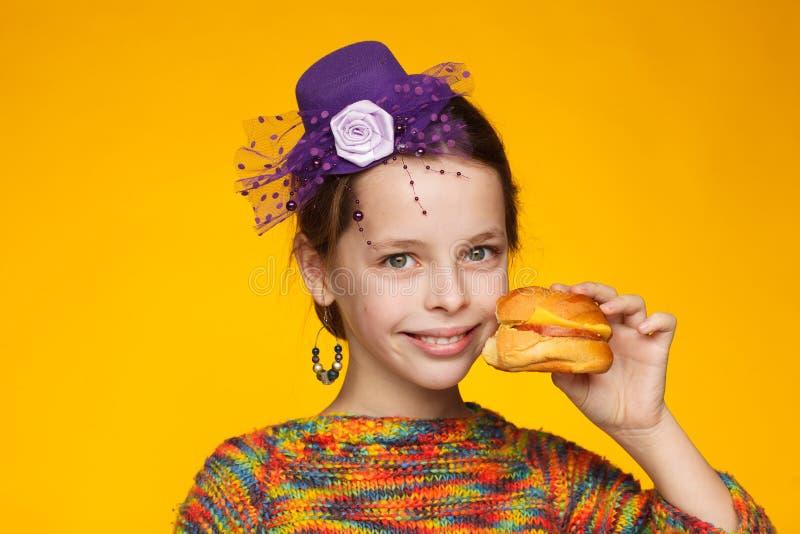 Портрет радостной восьмилетней девочки в миниатюрной шляпе, разноцветный свитер с сэндвичем в руке стоковая фотография