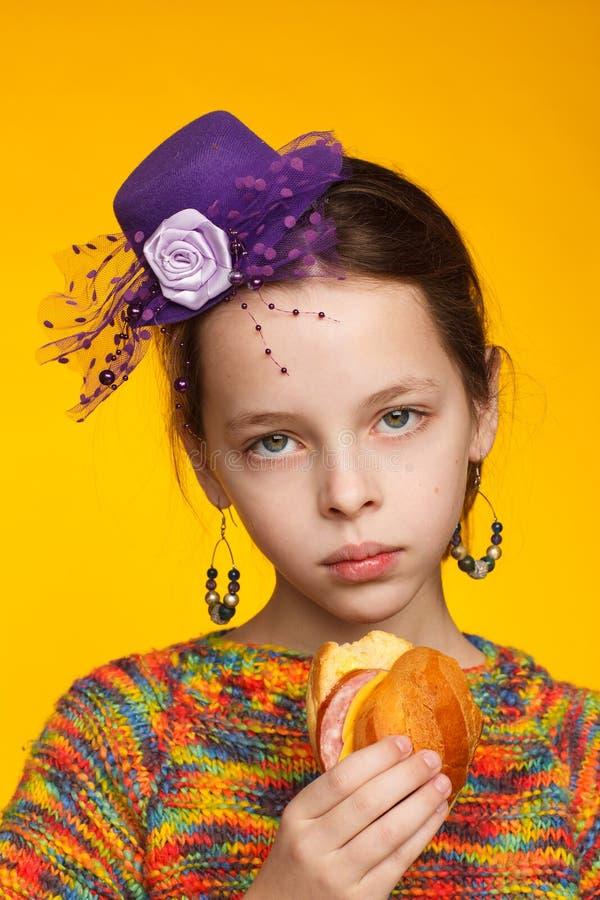 Портрет радостной восьмилетней девочки в миниатюрной шляпе, разноцветный свитер с сэндвичем в руке стоковое изображение rf