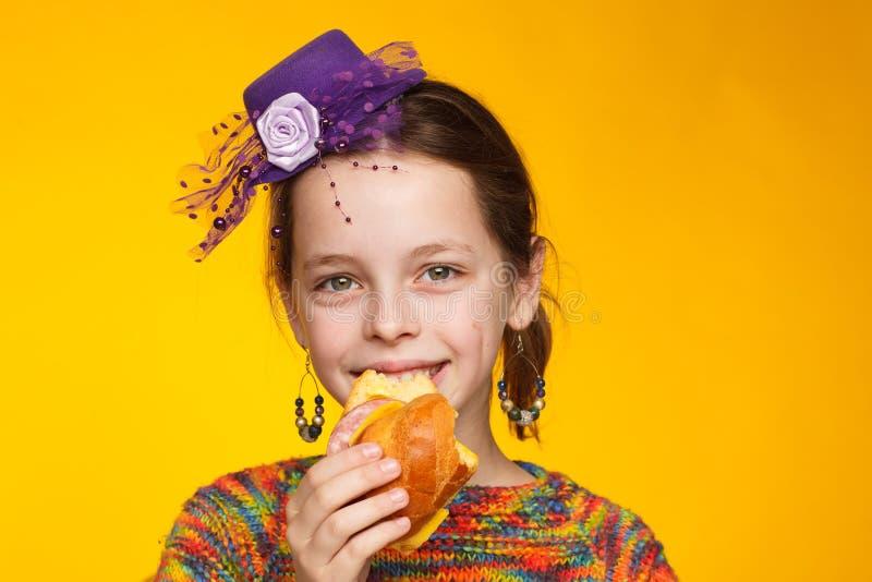Портрет радостной восьмилетней девочки в миниатюрной шляпе, разноцветный свитер с сэндвичем в руке стоковое изображение