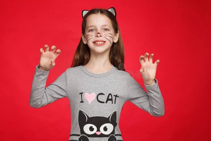 Портрет радостной восьмилетней девочки в платье с кошачьим узором и макияжем для кошек стоковая фотография