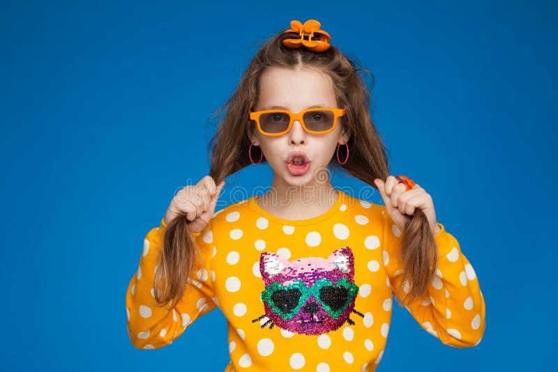 Портрет радостной восьмилетней девочки в ярком свитере с изображением кота, в очках и с фотоальбомом в руках стоковое фото rf