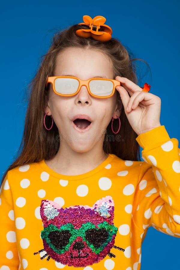 Портрет радостной восьмилетней девочки в ярком свитере с изображением кота, в очках и с фотоальбомом в руках стоковое изображение rf