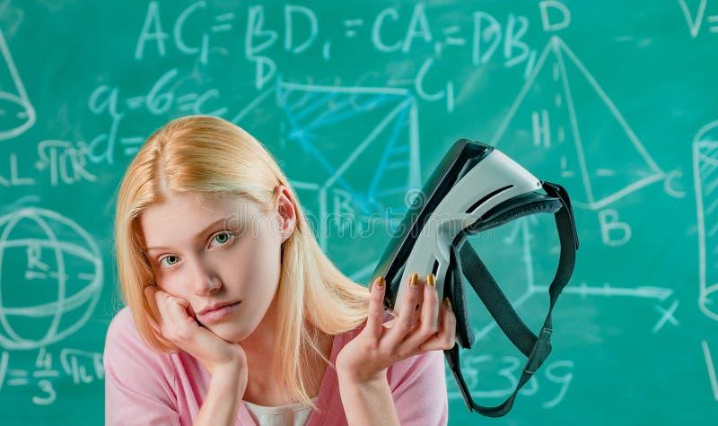 Портрет разочарованного белокурого студента женщины держа шлемофон виртуальной реальности на зеленой предпосылке доски стоковое изображение rf