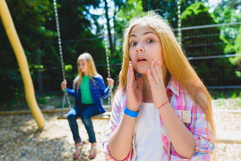 Портрет ребенка обиды на парке На предпосылке другая девушка ехать качание стоковые изображения