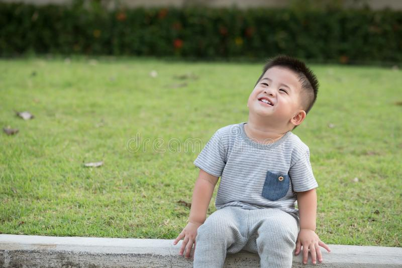 Портрет ребенка улыбки азиатского сидя на краю тропы в парке стоковые фото