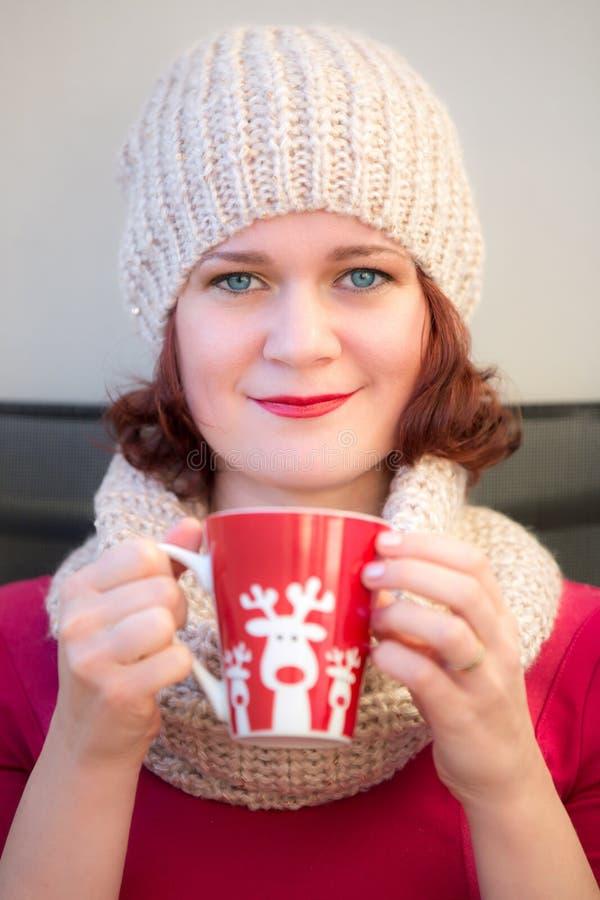 Портрет рождества девушки в связанной бежевой крышке и шарфе на шеи Женщина одела в красных и с красных владениях губ в h стоковая фотография rf