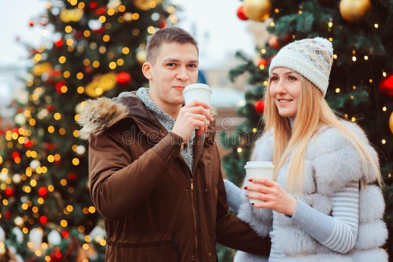 портрет рождества счастливых пар при горячие обдумыванные вино или чай идя на улицы города украшенные на праздники стоковое фото rf